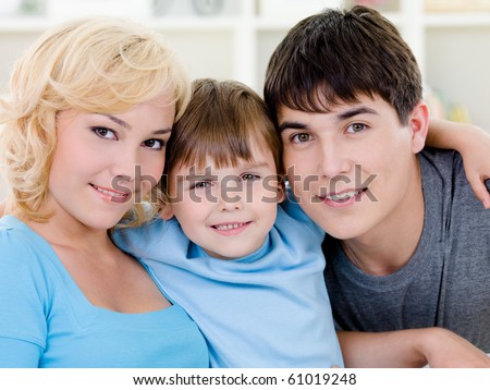 Close-up portrait of happy smiling cheerful family with son - indoors - stock photo