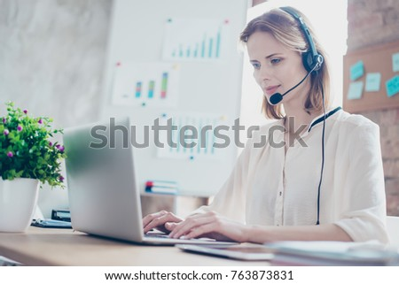 Close up portrait of happy smiling confident experienced qualified young professional operator of call center, she is sitting at the table and answering questions online using computer