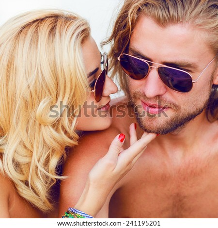 Close up portrait of happy smiling couple in love on the sunny beach. Wearing stylish sunglasses. Enjoying Summer Vacation.  - stock photo
