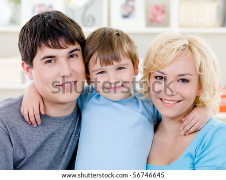 Close-up portrait of happy smiling family with little son - indoors - stock photo