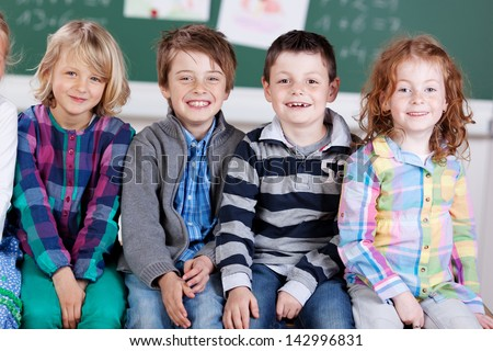 Close up portrait of happy students sitting in the classroom