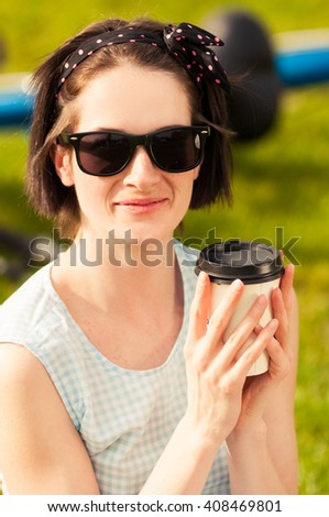 Close-up portrait of happy woman with sunglasses and coffee smiling and resting outside - stock photo