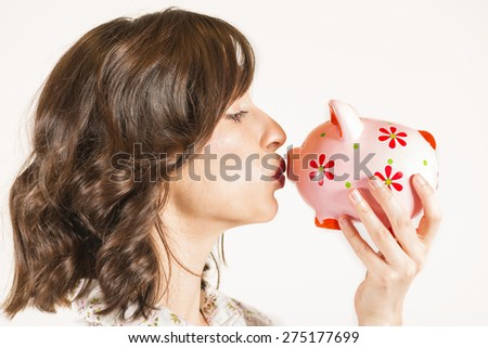 Close up portrait of happy young beautiful woman kissing pink piggy bank, studio shot on white background - stock photo