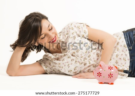 Close up portrait of happy young beautiful woman laying down looking at pink piggy bank, studio shot on white background - stock photo