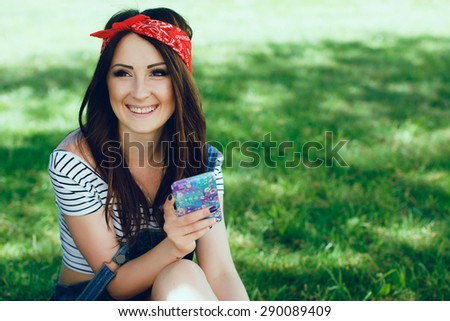 Close-up portrait of happy young brunette woman, sitting on the grass with mobile phone. Wearing red bandana and striped top. Sunny day. Copy space. - stock photo