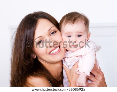 Close-up portrait of happy young mother with her newborn baby - indoors - stock photo