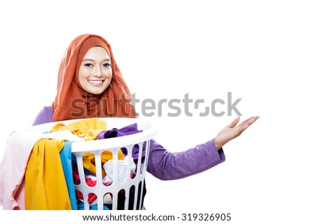 close up portrait of housewife wearing hijab carrying laundry basket full of dirty clothes and presenting copy space isolated on white - stock photo