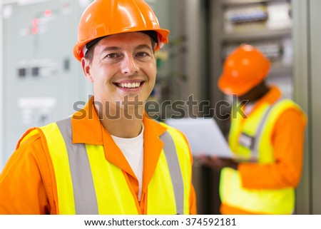 close up portrait of industrial technician in front of co-worker - stock photo