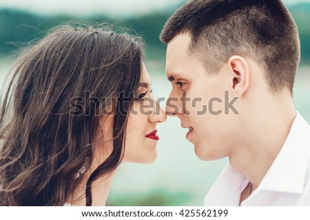 Close up portrait of kissing couple against green trees in the park. Beautiful young woman with long dark wavy hair kissing handsome man outdoors. Cute newlyweds on their wedding ceremony. - stock photo