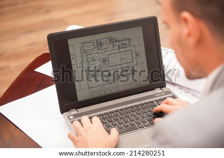 Close-up portrait of laptop with blueprints, architect sitting from behind working on architectural plan, interior shot - stock photo