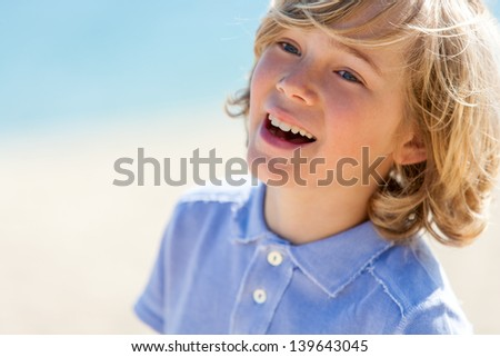 Close up portrait of laughing blond boy outdoors. - stock photo