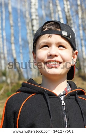 close-up portrait of laughing little boy in spring birch grove