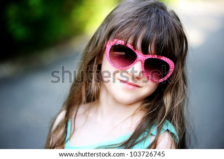 Close-up portrait of little child girl in pink sunglasses posing outdoors on a sunny day