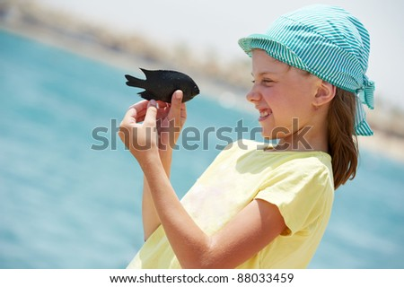 close up portrait of little girl examining little fish from red sea - stock photo