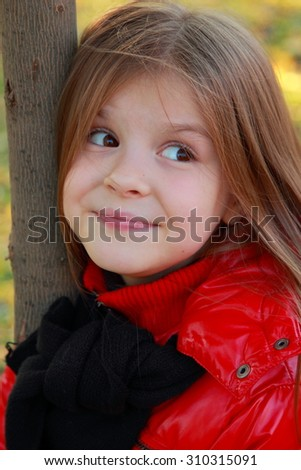Close up portrait of little girl in warm red coat smiling against the background of fallen leaves/Image of adorable little girl with autumn leaves in the beauty par