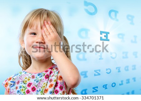 Close up portrait of little girl reading eye chart. Young kid testing one eye on block letter vision chart.