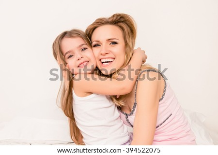 Close up portrait of little girl smiling and huging her mom - stock photo