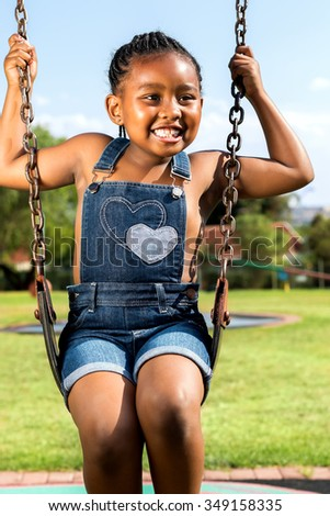 Close up portrait of little smiling African girl swinging in park.