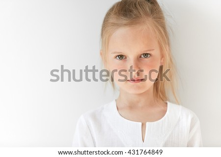Close up portrait of little white-skinned girl looks straight forward and closely watching you. Blond baby stares at you showing her interest and curiosity as well as readiness to listen. - stock photo