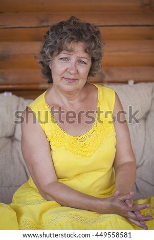 Close up portrait of lovely middle aged woman in yellow dress