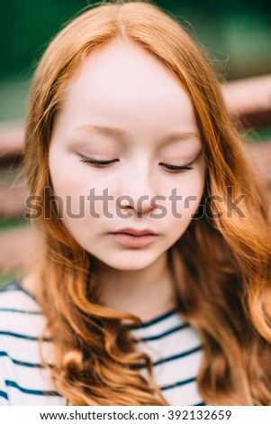 Close-up portrait of lovely thoughtful girl with long curly red hair in summer park. Outdoor portrait of a red-haired teenage girl. Adorable young redhead longhaired woman - stock photo