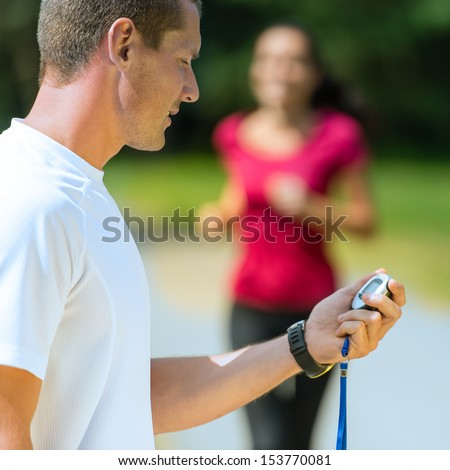 Close up portrait of male coach timing runner - stock photo
