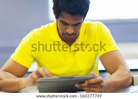 close up portrait of male indian college student using tablet computer - stock photo