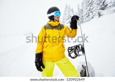 Close up portrait of male snowboarder wearing helmet with glasses, yellow jacket and pants, black gloves standing with snowboard in one hand  against blizzard - extreme sports concept - stock photo