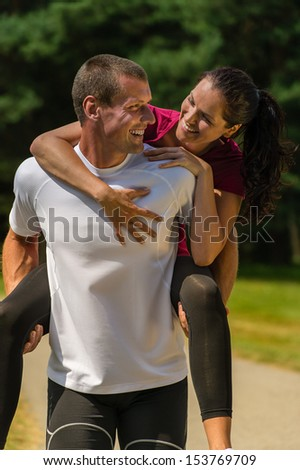 Close up portrait of man giving piggyback ride his girlfriend - stock photo