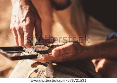 Close up portrait of man using compass for directions. Focus on compass in hands of a male hiker. - stock photo