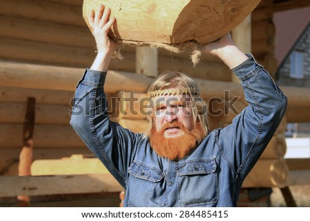close-up portrait of man with a log in his hand against the background of the new log house on a sunny day - stock photo
