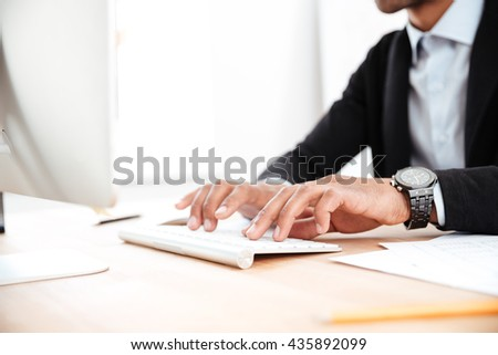 Close-up portrait of men's hands typing on the keyboard at the office