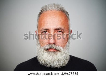 close-up portrait of middle-aged man with grey-haired beard over grey background