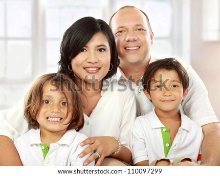 close up portrait of mixed race family in the living room - stock photo
