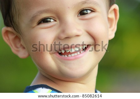 close up portrait of mixed race kid smiling to the camera - stock photo