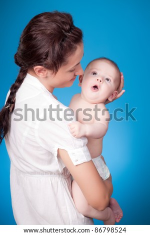 close-up portrait of mother with a baby, studio shot - stock photo