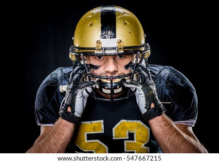 Close-up portrait of muscular american football player in uniform adjusting helmet isolated on black