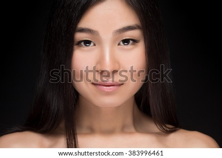 Close-up portrait of naked Asian woman smiling and looking at camera. Happy lady with long black hair posing in studio isolated on dark background. - stock photo
