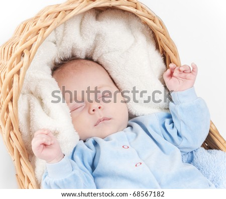 Close-up portrait of newborn baby sleeping sleeps in basket with towel. Beautiful baby sleeping on white in studio isolated over white background. - stock photo