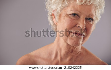 Close-up portrait of old caucasian female face against grey background. Senior woman with wrinkled skin looking at camera with copy space. - stock photo
