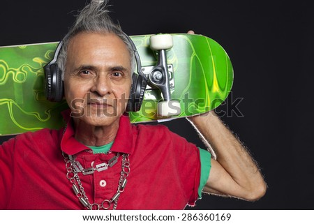 Close-up portrait of old man with skateboard - stock photo