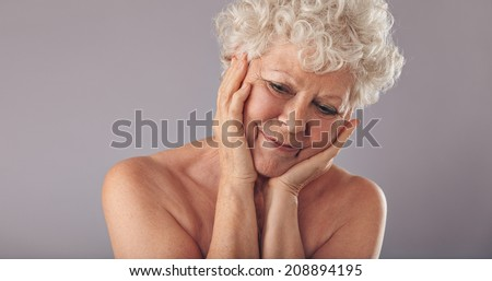 Close-up portrait of old woman holding her face and looking down in thought. Thoughtful senior lady on grey background. - stock photo