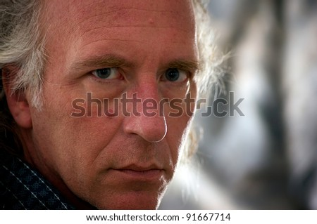 Close up portrait of older blue eyed white male looking directly at viewer. - stock photo