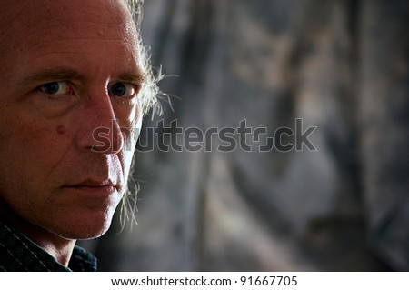 Close up portrait of older blue eyed white male looking directly at viewer in corner of frame. - stock photo