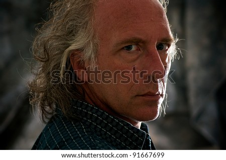 Close up portrait of older blue eyed white male looking over shoulder directly at viewer. - stock photo