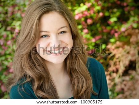 Close up Portrait of One Beautiful and Cheerful Young Lady in a Teal Blouse, Happy Outside in the Spring Garden Setting with Space for Copy or Text. - stock photo