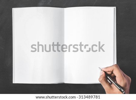 close up portrait of open book with blank page and hands holding a pen with black board for background - stock photo