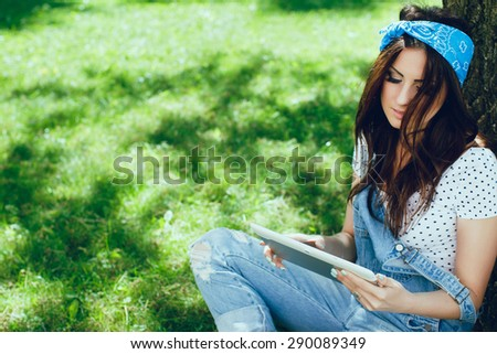 Close-up portrait of pretty brunette girl, sitting in the park, looking at tablet. Wearing blue bandana, denim jumpsuit and top in speckled. Sunny day. Copy space. - stock photo