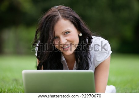 Close-up portrait of pretty female lying on grass using laptop