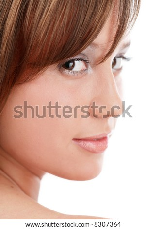 Close-up portrait of pretty girl looking over her shoulder and smiling